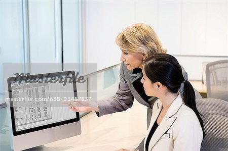 Businesswoman reviewing co-worker's work on monitor Stock Photo - Premium Royalty-Free, Image code: 635-03457837