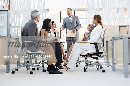 Business people having meeting in middle of office Stock Photo - Premium Royalty-Free, Image code: 635-03457846
