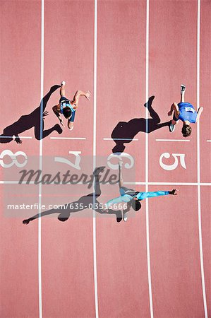 Runner crossing finishing line on track Stock Photo - Premium Royalty-Free, Image code: 635-03515666