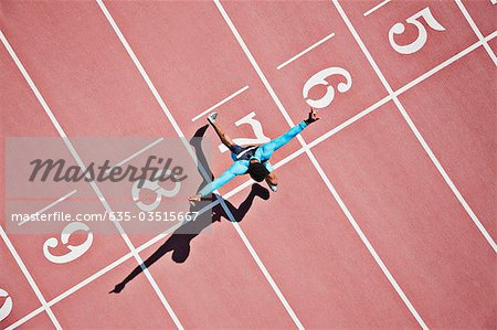 Runner crossing finishing line on track Stock Photo - Premium Royalty-Free, Image code: 635-03515667