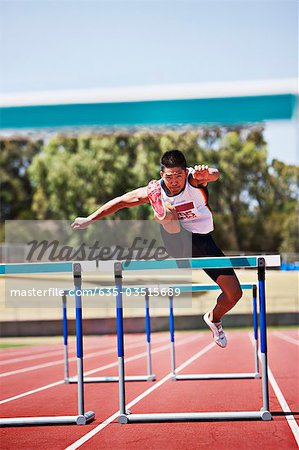 Runner jumping hurdles on track Stock Photo - Premium Royalty-Free, Image code: 635-03515689