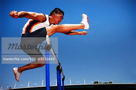 Runner jumping hurdles on track Stock Photo - Premium Royalty-Free, Image code: 635-03515690