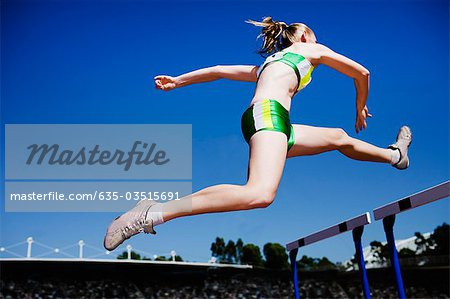 Runner jumping hurdles on track Stock Photo - Premium Royalty-Free, Image code: 635-03515691