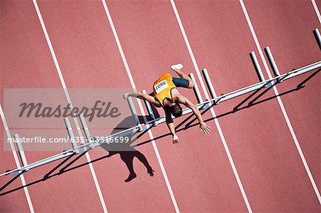 Runner jumping hurdles on track Stock Photo - Premium Royalty-Free, Image code: 635-03515699