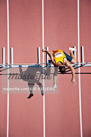 Runner jumping hurdles on track Stock Photo - Premium Royalty-Free, Image code: 635-03515700
