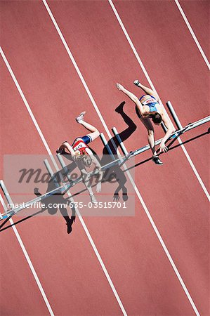 Runners jumping hurdles on track Stock Photo - Premium Royalty-Free, Image code: 635-03515701