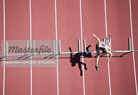 Runner jumping hurdles on track Stock Photo - Premium Royalty-Free, Image code: 635-03515702