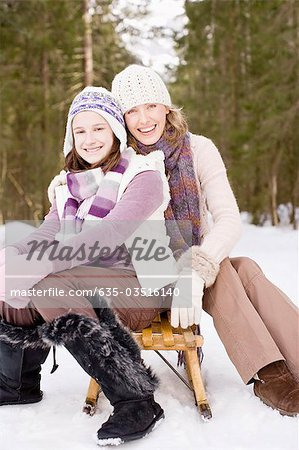 Mother and daughter sitting on sled in snow Stock Photo - Premium Royalty-Free, Image code: 635-03516140