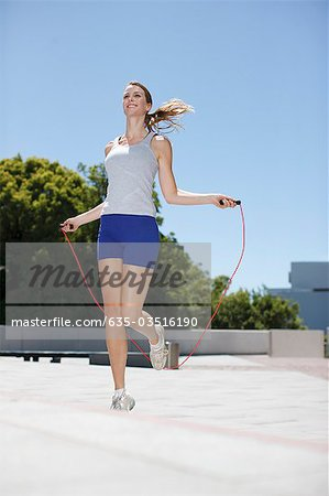 Woman skipping rope in urban plaza Stock Photo - Premium Royalty-Free, Image code: 635-03516190