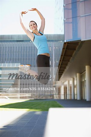 Woman jumping in urban setting Stock Photo - Premium Royalty-Free, Image code: 635-03516243