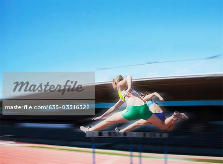Runners jumping over hurdles Stock Photo - Premium Royalty-Free, Image code: 635-03516322