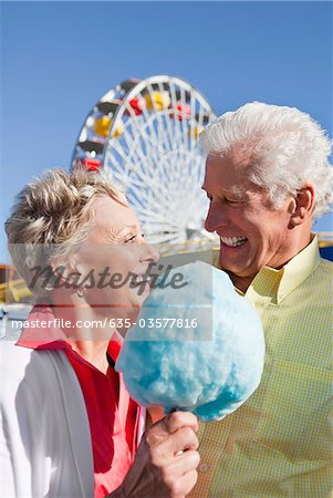 Smiling senior couple sharing cotton candy at amusement park Stock Photo - Premium Royalty-Free, Image code: 635-03577816