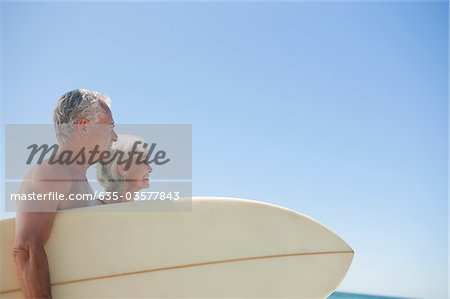 Senior couple with surfboard against blue sky Stock Photo - Premium Royalty-Free, Image code: 635-03577843