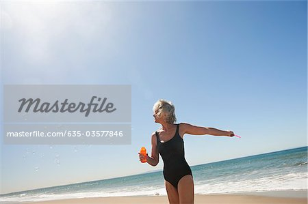 Senior woman blowing bubbles on beach Stock Photo - Premium Royalty-Free, Image code: 635-03577846
