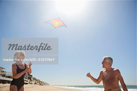 Senior couple flying kite on beach Stock Photo - Premium Royalty-Free, Image code: 635-03577847