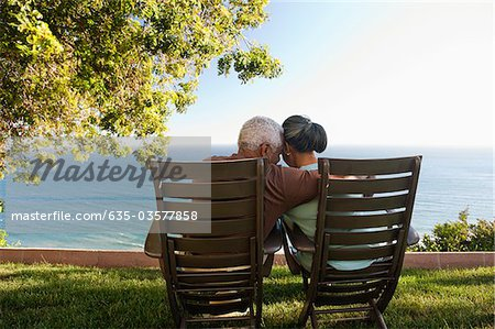 Senior couple hugging in lounge chairs on grass overlooking ocean Stock Photo - Premium Royalty-Free, Image code: 635-03577858