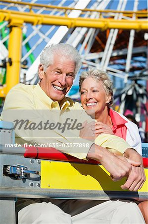 Smiling senior couple on amusement park ride Stock Photo - Premium Royalty-Free, Image code: 635-03577898
