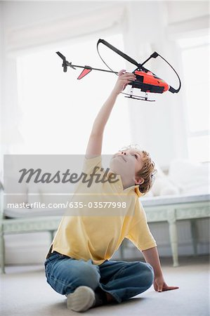 Boy playing with toy helicopter Stock Photo - Premium Royalty-Free, Image code: 635-03577998