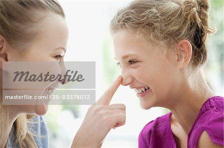 Smiling mother touching daughter's nose Stock Photo - Premium Royalty-Free, Image code: 635-03578072