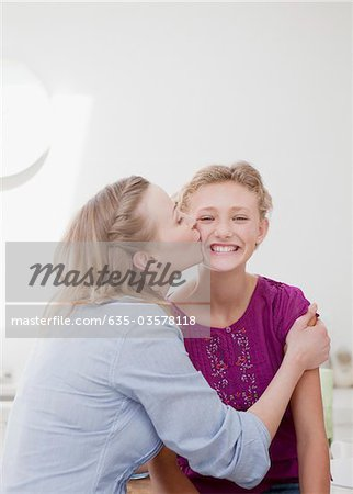 Mother hugging and kissing smiling daughter Stock Photo - Premium Royalty-Free, Image code: 635-03578118