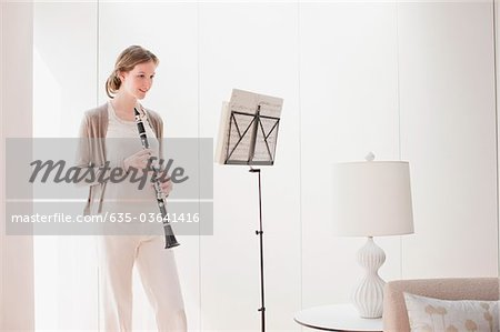 Woman holding clarinet and looking at sheet music Stock Photo - Premium Royalty-Free, Image code: 635-03641416