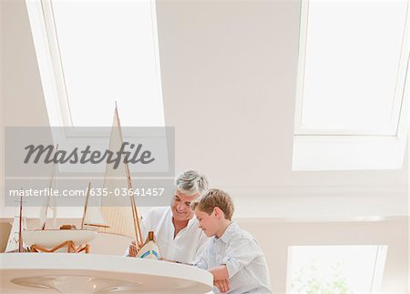 Father and son assembling model sailboat Stock Photo - Premium Royalty-Free, Image code: 635-03641457