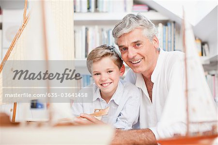 Smiling grandfather and grandson with model sailboats Stock Photo - Premium Royalty-Free, Image code: 635-03641458