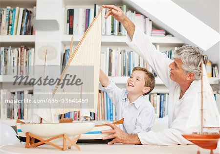 Grandfather and grandson looking at model sailboats Stock Photo - Premium Royalty-Free, Image code: 635-03641459