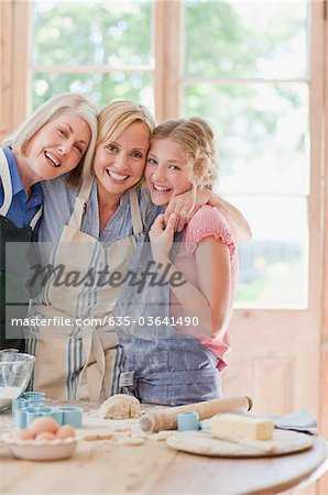 Smiling multi-generation females hugging and baking in kitchen Stock Photo - Premium Royalty-Free, Image code: 635-03641490