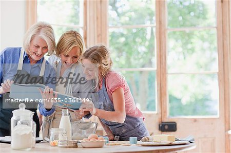 Multi-generation females looking at cookbook and baking in kitchen Stock Photo - Premium Royalty-Free, Image code: 635-03641491