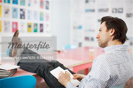 Businessman writing on notepad with feet up in office Stock Photo - Premium Royalty-Free, Image code: 635-03641580