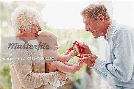 Grandparents holding baby with toy Stock Photo - Premium Royalty-Free, Image code: 635-03641862
