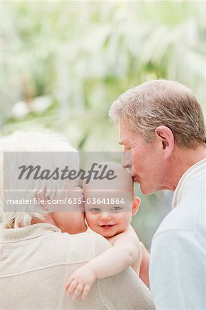 Grandparents holding and kissing smiling baby Stock Photo - Premium Royalty-Free, Image code: 635-03641864