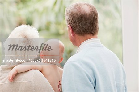 Grandparents holding baby and looking out window Stock Photo - Premium Royalty-Free, Image code: 635-03641865