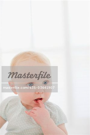 Curious baby with finger in mouth Stock Photo - Premium Royalty-Free, Image code: 635-03641907