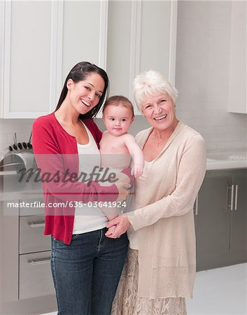 Smiling grandmother and mother holding baby in kitchen Stock Photo - Premium Royalty-Free, Image code: 635-03641924