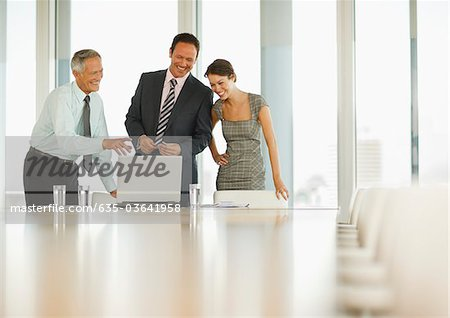 Smiling business people looking at laptop in conference room Stock Photo - Premium Royalty-Free, Image code: 635-03641958