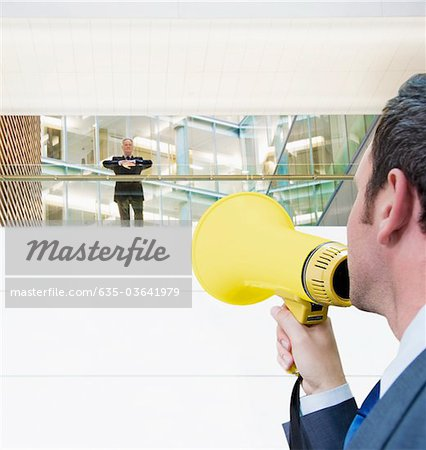 Businessman with bullhorn yelling up at boss Stock Photo - Premium Royalty-Free, Image code: 635-03641979