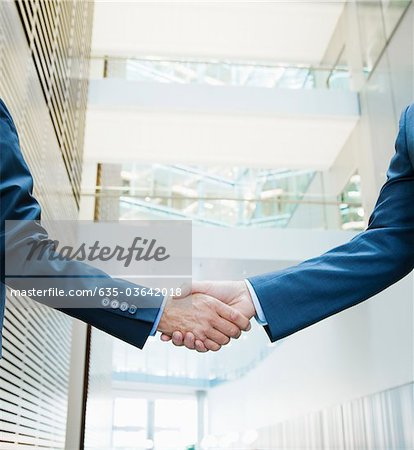 Businessmen shaking hands in lobby Stock Photo - Premium Royalty-Free, Image code: 635-03642018