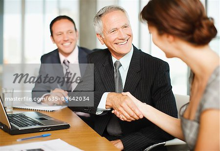 Smiling business people shaking hands in conference room Stock Photo - Premium Royalty-Free, Image code: 635-03642034