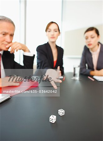 Business people throwing dice on conference room table Stock Photo - Premium Royalty-Free, Image code: 635-03642042