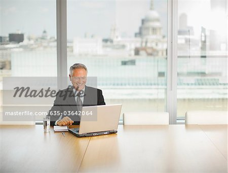 Smiling businessman using laptop in conference room Stock Photo - Premium Royalty-Free, Image code: 635-03642064