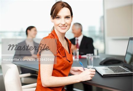 Smiling businesswoman with laptop in conference room Stock Photo - Premium Royalty-Free, Image code: 635-03642068