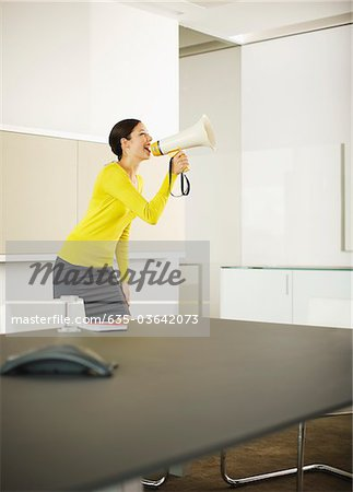 Businesswoman shouting in bullhorn in conference room Stock Photo - Premium Royalty-Free, Image code: 635-03642073