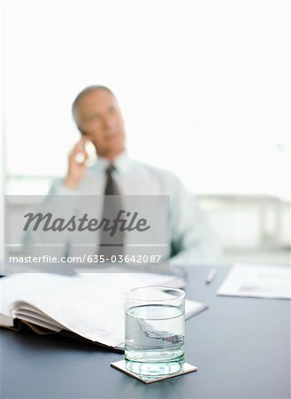 Pensive businessman sitting at desk in office Stock Photo - Premium Royalty-Free, Image code: 635-03642087