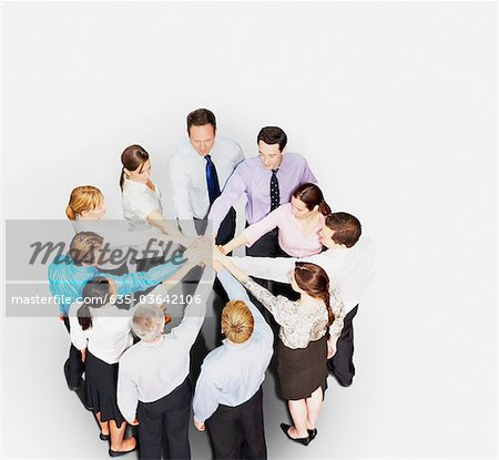 Business people in circle stacking hands Stock Photo - Premium Royalty-Free, Image code: 635-03642106