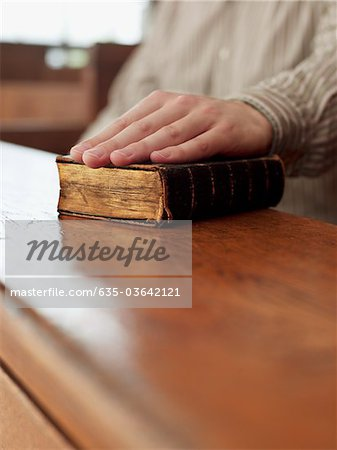 Hand of witness on Bible in courtroom Stock Photo - Premium Royalty-Free, Image code: 635-03642121