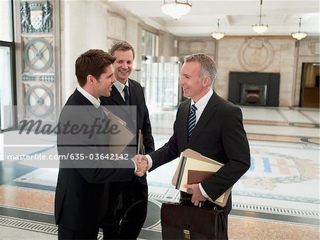 Smiling lawyers with files shaking hands in lobby Stock Photo - Premium Royalty-Free, Image code: 635-03642142