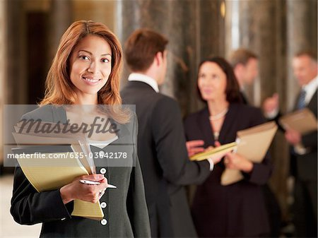 Smiling lawyer holding files in corridor Stock Photo - Premium Royalty-Free, Image code: 635-03642178