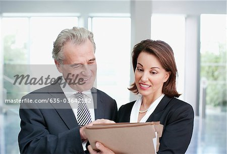 Smiling business people reviewing file in office Stock Photo - Premium Royalty-Free, Image code: 635-03642182